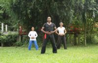 three people practicing qi gong in garden