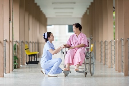 woman in a wheel chair in hospital with nurse